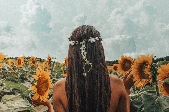 dívka s květinovým věnečkem ve vlasech v lánu slunečnic